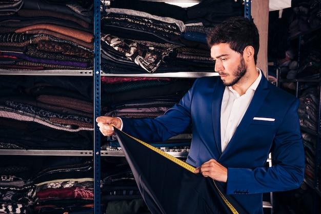Portret van een mode-ontwerper nemen van de meting van de stof in zijn winkel