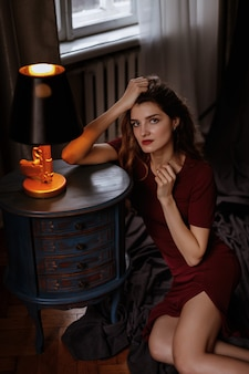Portret van een model in een bordeauxrode jurk in de avond in het appartement. paris stijl