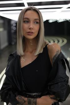 Portret van een modelmeisje in een zwarte bodysuit-windjack en heldere zilveren pailletten op het lichaam dat binnenshuis staat met helder kunstlicht aan het plafond en naar de zijkant kijkt