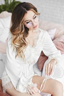 Portret van een modelmeisje in elegante brillen en witte satijnen pyjama's in het gezellige interieur in de ochtend