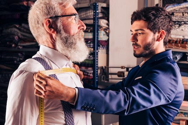 Portret van een modeontwerper die de borst van zijn klant meet in zijn atelier