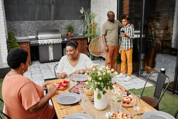 Portret van een moderne afro-amerikaanse familie die buiten geniet van een diner op de kopieerruimte van het terras