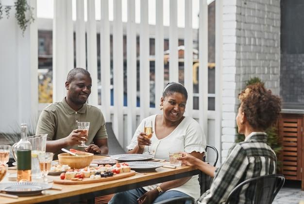 Portret van een moderne afro-amerikaanse familie die buiten samen geniet van een drankje tijdens het diner