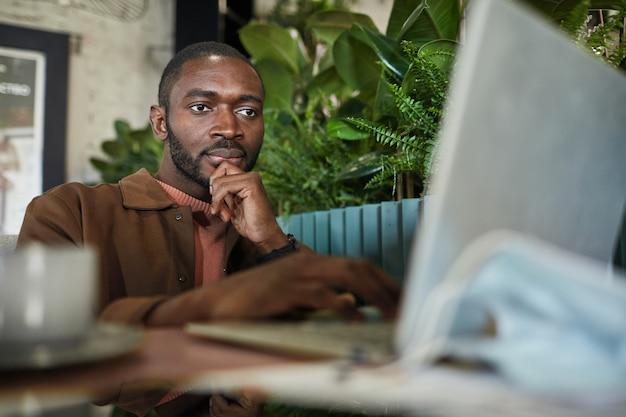 Portret van een moderne afro-amerikaanse man die met een laptop werkt terwijl hij aan tafel zit in een milieuvriendelijk groen café-interieur, kopieer ruimte