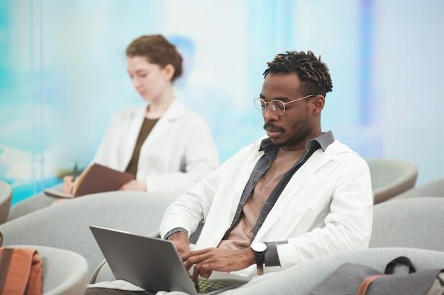 Portret van een moderne afro-amerikaanse man met een laboratoriumjas tijdens het gebruik van een laptop in een coworking-centrum op de medische universiteit, kopieer ruimte