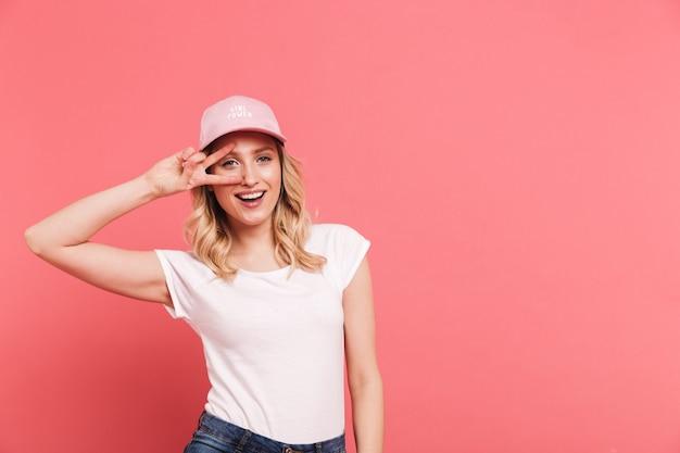Portret van een moderne, gekrulde vrouw met een casual t-shirt en pet die lacht en een vredesteken toont dat over een roze muur is geïsoleerd