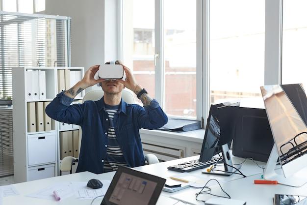Portret van een moderne it-ontwikkelaar die een vr-headset draagt terwijl hij aan augmenter reality-games en -software werkt, kopieer ruimte