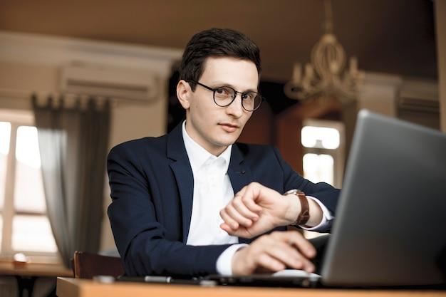 Portret van een moderne jonge manager die in zijn loftkantoor werkt en praat over welk uur het is.