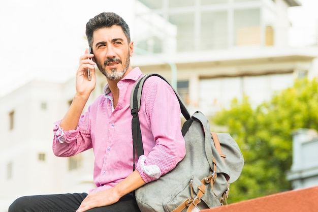 Portret van een moderne man in het roze shirt met zijn rugzak praten op mobiele telefoon