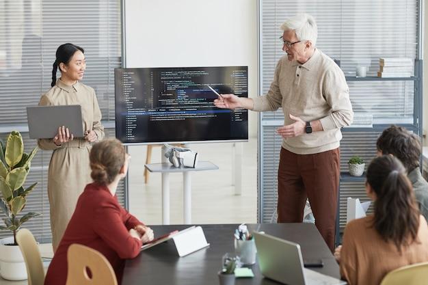 Portret van een moderne senior man die op kantoor een presentatie geeft aan het it-team en naar code op het scherm wijst, kopieer ruimte