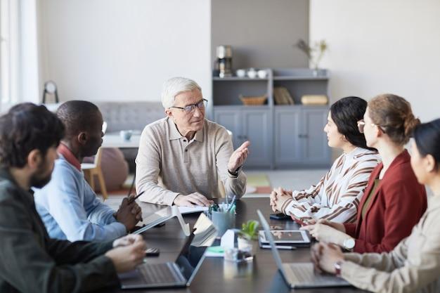 Portret van een moderne senior zakenman die met een groep mensen praat tijdens een vergadering aan tafel in het kantoor