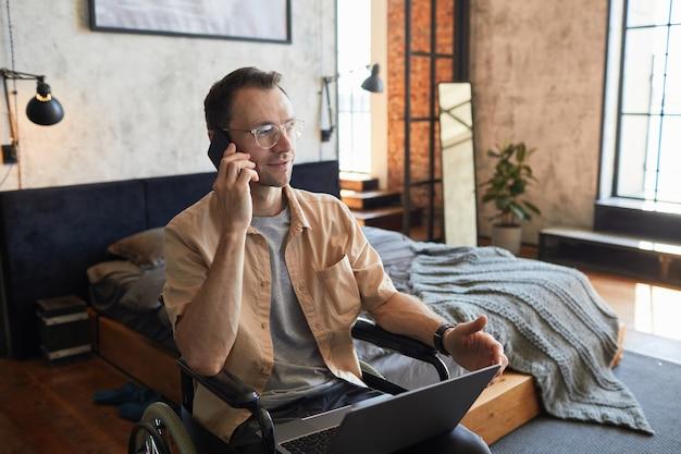 Portret van een moderne volwassen man met een handicap die via een smartphone spreekt terwijl hij thuis werkt in een designinterieur, kopieer ruimte