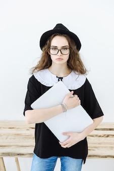 Portret van een moderne vrouwelijke ontwerper met een hoed en een bril die een laptop vasthoudt en naar de voorkant kijkt