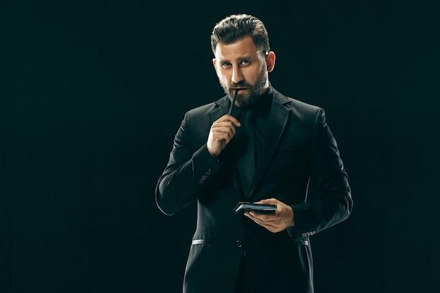 Portret van een modieuze jonge man met stijlvol kapsel in trendy pak poserend over zwarte muur