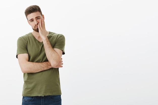 Portret van een moe en onverschillig knap vriendje dat wordt gehersenspoeld tijdens een ruzie met zijn gezicht en uitgeput en verveeld kijkt met een uitgeput en bedroefd gezicht over een witte muur