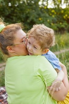 Portret van een moeder die haar jonge zoon met speciale behoeften knuffelt in een zomerpark. onbekwaamheid. infantiele verlamming. zomerwandelingen in de frisse lucht.