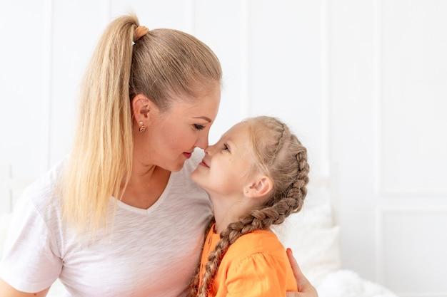Portret van een moeder en dochter die naar elkaar kijken, het concept van liefde en moederschap of moederdag