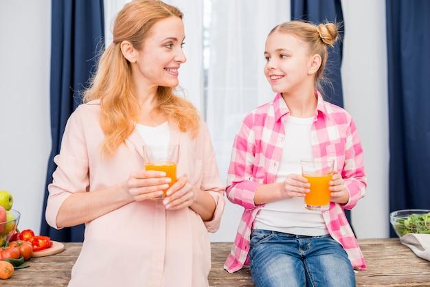Portret van een moeder en dochter houden glas sap in de hand te kijken naar elkaar