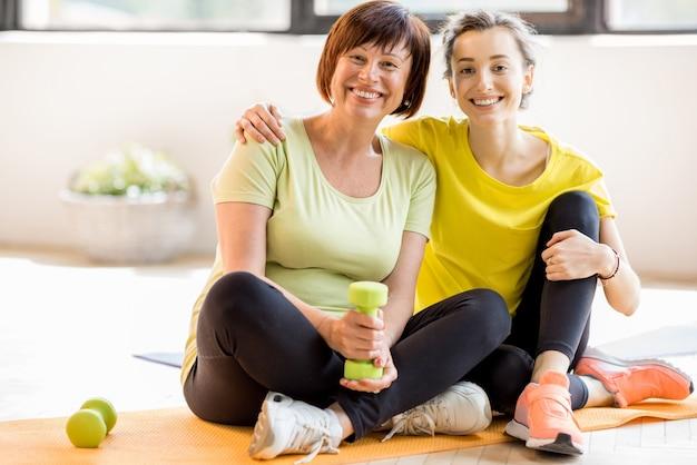 Portret van een moeder en dochter in sportkleding die samen zitten na de training binnenshuis