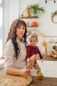 Portret van een moeder en een baby in de keuken tijdens een maaltijd