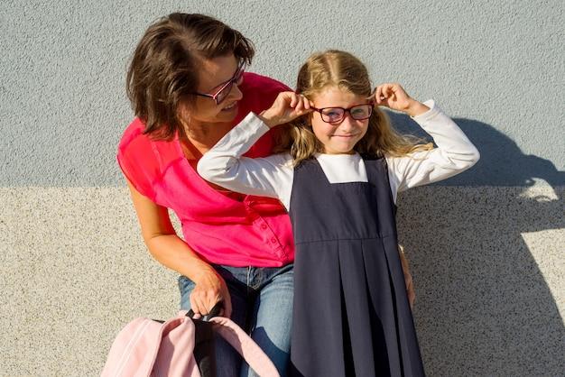 Portret van een moeder en een klein schoolmeisje met een bril