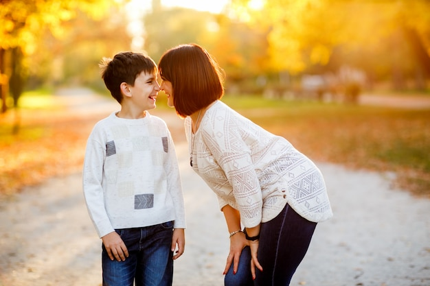 Portret van een moeder en een zoon bij de herfstpark