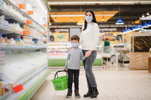 Portret van een moeder en haar zoontje die een beschermend gezichtsmasker dragen in een supermarkt tijdens de coronavirusepidemie of griepuitbraak. lege ruimte voor tekst.