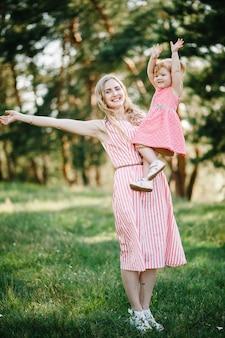 Portret van een moeder houdt dochter op handen op de natuur op zomervakantie. moeder en meisje spelen in het park bij zonsondergang. concept van vriendelijke familie. detailopname.