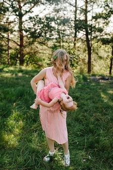 Portret van een moeder houdt, geeft over en draait de dochter op handen op de natuur op zomervakantie. moeder en meisje spelen in het park bij zonsondergang. concept van vriendelijke familie. detailopname.