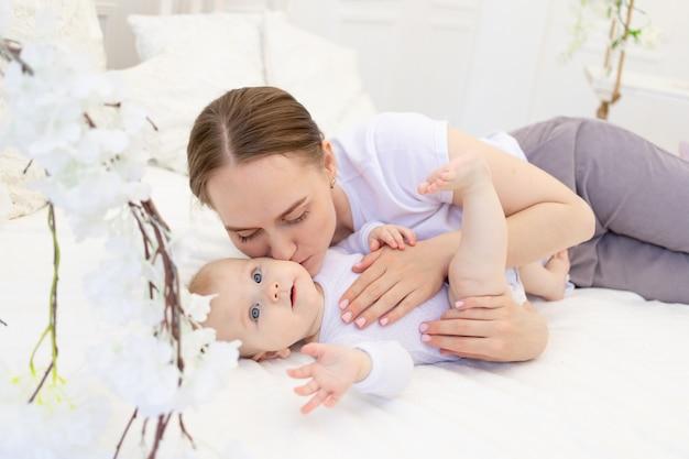 Portret van een moeder met een baby, een moeder kust een kind en knuffelt hem zachtjes op een wit bed thuis, moederliefde en zorg