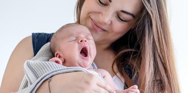 Portret van een moeder met een slaperige pasgeboren zoon op een witte achtergrond.