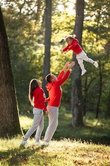 Portret van een moeder, vader houdt, werpt en draait de dochter op handen lopen op de natuur op herfstdagvakantie.