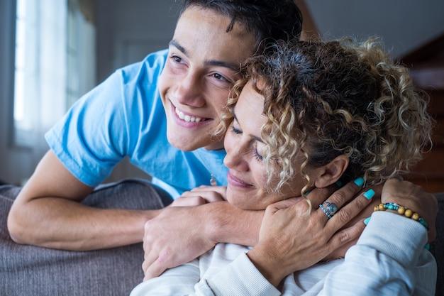 Portret van een moeder van middelbare leeftijd die tijd doorbrengt met tienerzoon, familieleden die thuis knuffelen, volwassen attent duizendjarig dankbaar kind gewikkeld in een plaid of warme trui liefdevolle mama zorgzaam