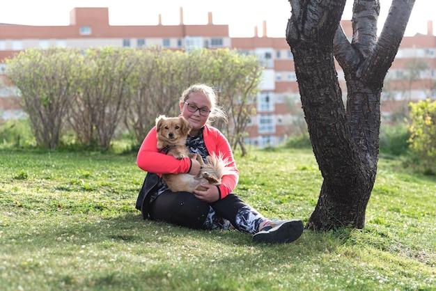 Portret van een mollig blond meisje met bril, zittend op het gazon met haar hond.