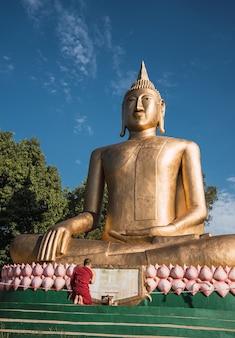 Portret van een monnik die bidt met de grootste boeddha in zuid-amerika