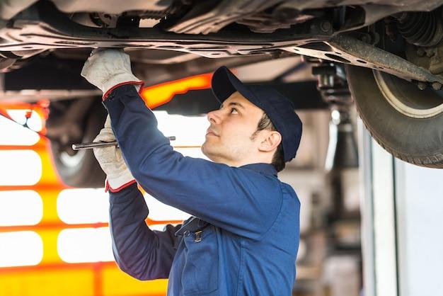 Portret van een monteur die een auto in zijn garage herstelt
