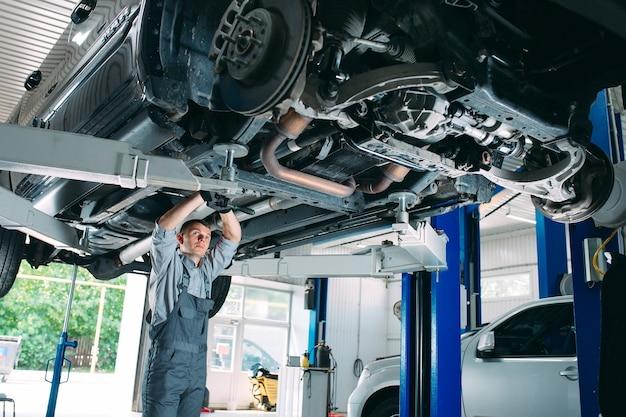 Portret van een monteur die een opgeheven auto herstelt.