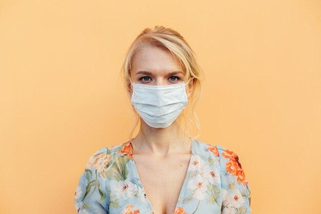 Portret van een mooi aantrekkelijk charmant meisje in een mooie jurk close-up met een gezichtsmasker ter bescherming van het virus geïsoleerd op een oranje pastel achtergrond