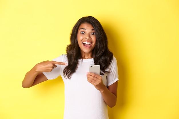 Portret van een mooi afro-amerikaans meisje dat met de vinger naar de mobiele telefoon wijst om iets opwindends te laten zien...