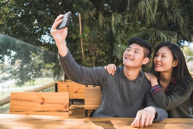 Portret van een mooi aziatisch paar dat goede tijd heeft en een selfie met mobiele telefoon in coffeeshop neemt.