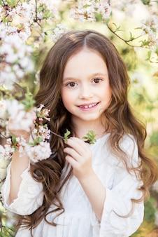 Portret van een mooi babymeisje in een bloeiende lentetuin. een meisje op een achtergrond van witte bloemen.