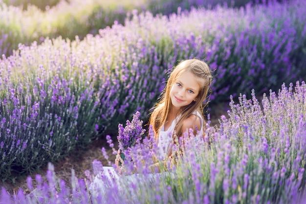Portret van een mooi babymeisje in een lavendelgebied. zomerfoto in paarse kleuren.