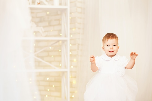 Portret van een mooi babymeisje in een witte jurk in het interieur met kerstversiering