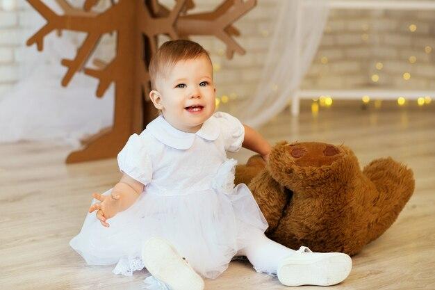Portret van een mooi babymeisje met een zachte bruine teddybeer in het interieur met kerstversiering.
