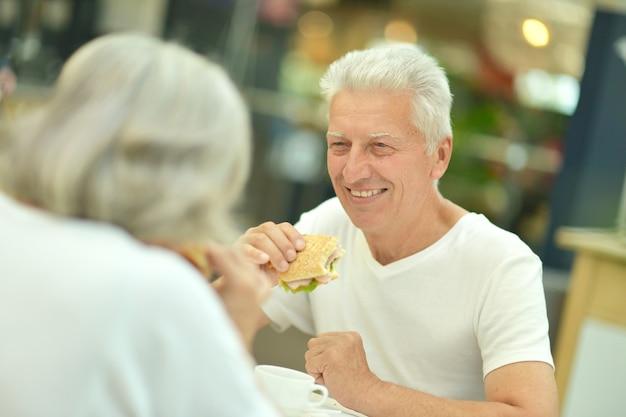 Portret van een mooi bejaarde echtpaar dat fastfood eet