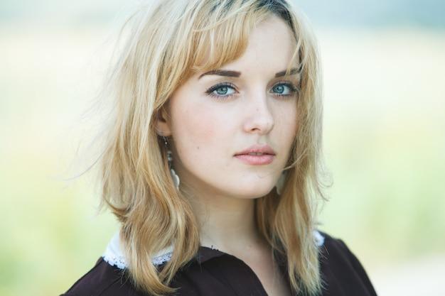 Portret van een mooi blond haarmeisje buiten