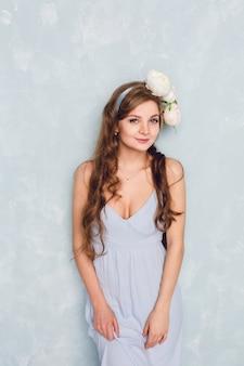 Portret van een mooi blond meisje met krullend haar dat zich in een studio met een circlet van pioenen bevindt. ze draagt een lichtblauwe zijden jurk. ze ziet er teder en lief uit