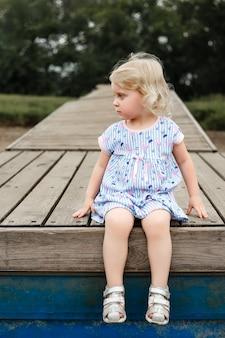 Portret van een mooi blond meisje, zittend op een houten pantone. hoge kwaliteit foto