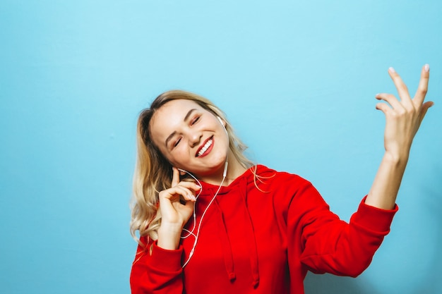 Portret van een mooi blond opgewonden meisje dat aan muziek in hoofdtelefoons luistert en over blauwe muur danst