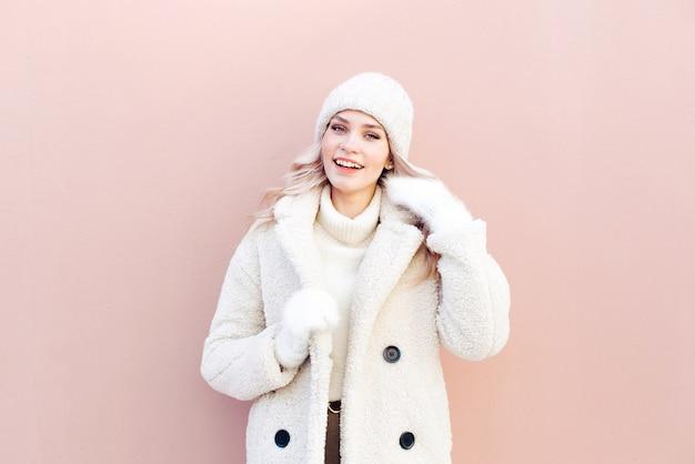 Portret van een mooi blondemeisje in de winterkleren op een achtergrond van een roze muur in de straat